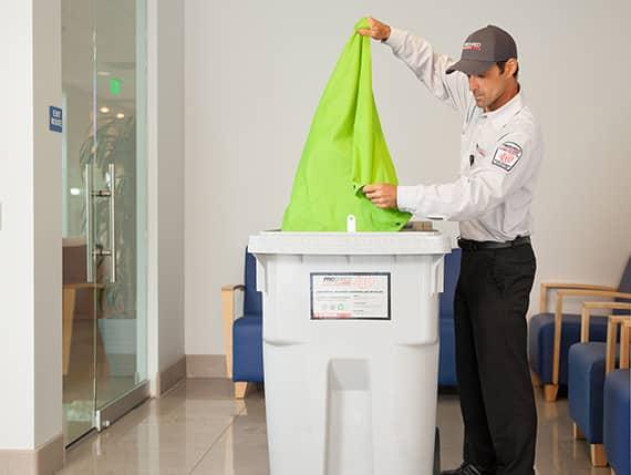 Service Tech using a Proshred bin.