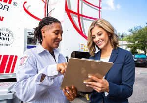 Shredding company employee and businesswoman discussing a contract outside by a mobile shred truck.