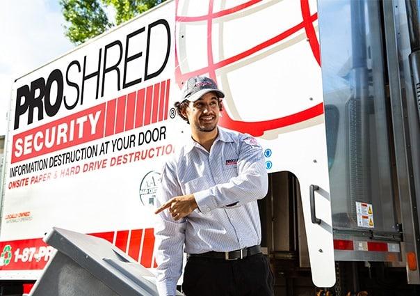 Employee pushing a secure bin on a residential shredding pickup.