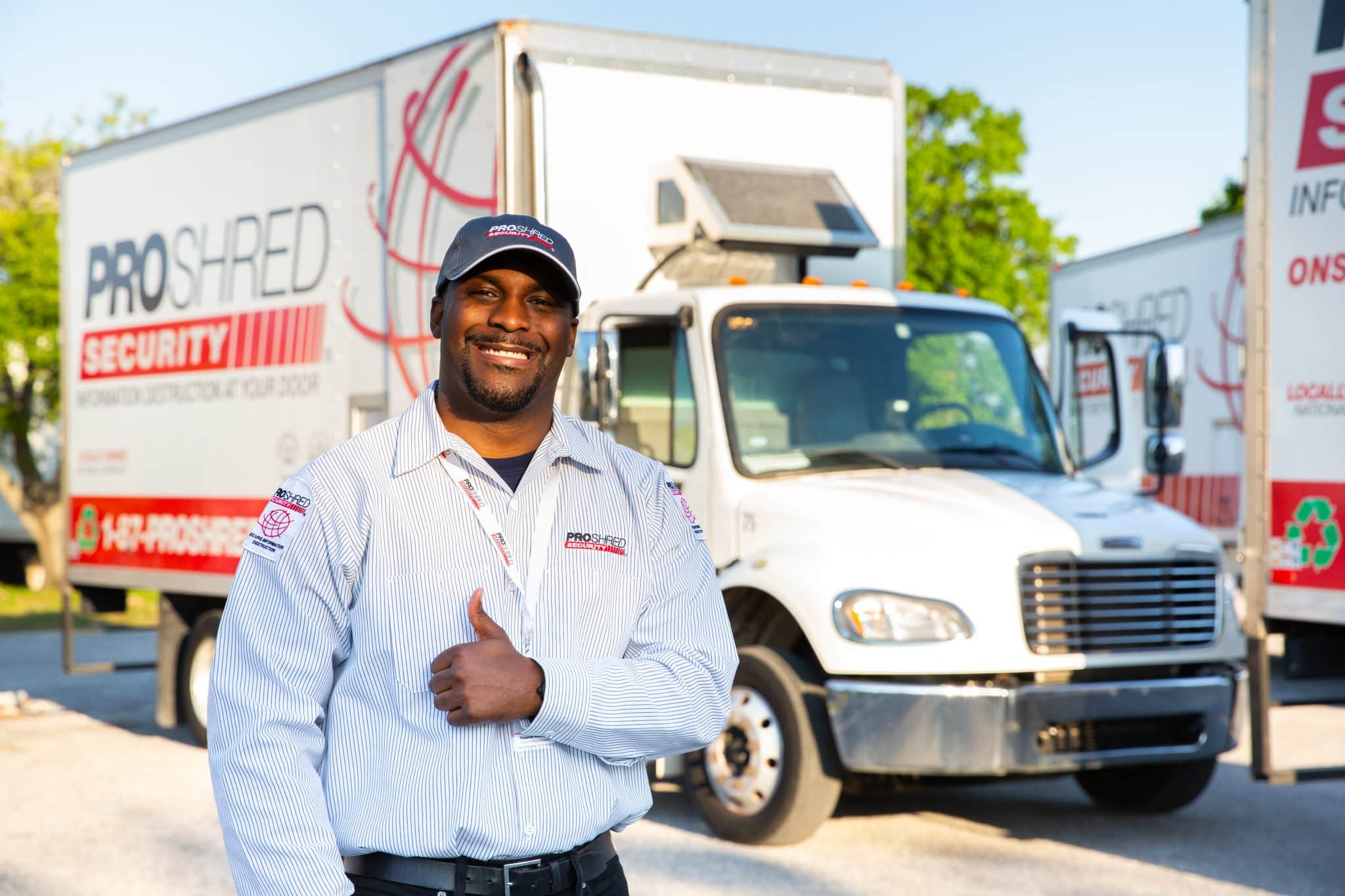PROSHRED Security employee giving a thumbs up and smiling in front of a shredding truck.